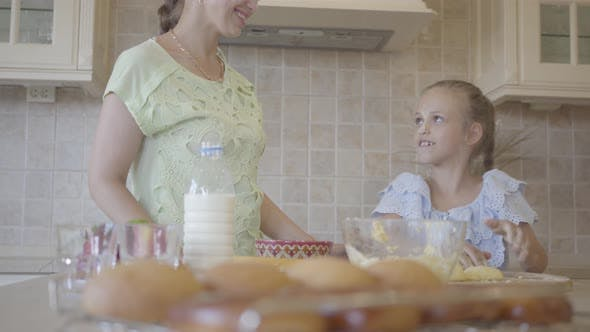 Cover Image for Young Woman and Her Little Daughter Cooking Cakes at Home in the Kitchen