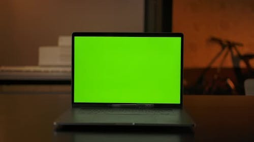 Laptop Computer Showing Green Chroma Key Screen Stands on a Desk in Living Room
