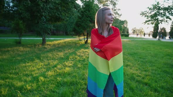 Cover Image for Smiling Woman Holding Rainbow Flag Around Body.