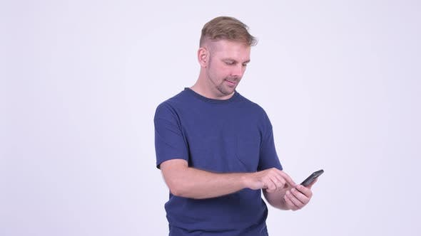 Thumbnail for Portrait of Happy Blonde Man Using Phone and Getting Good News