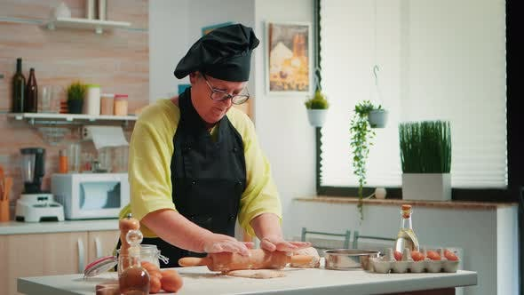 Woman Chef Using Wooden Rolling Pin