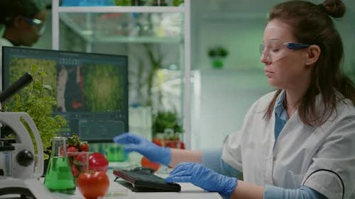 Pharmaceutical Chemist Examining Tomato for Microbiology Experiment