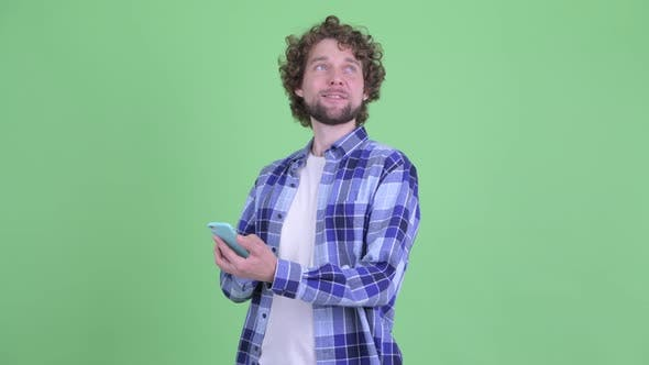 Thumbnail for Happy Young Bearded Hipster Man Thinking While Using Phone