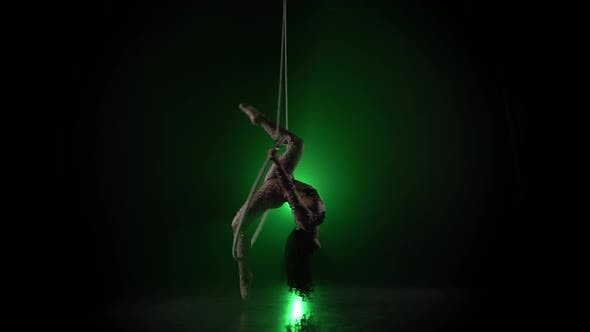 Thumbnail for Aerial Acrobat in the Ring. A Young Girl Performs the Acrobatic Elements in the Air Ring on Green