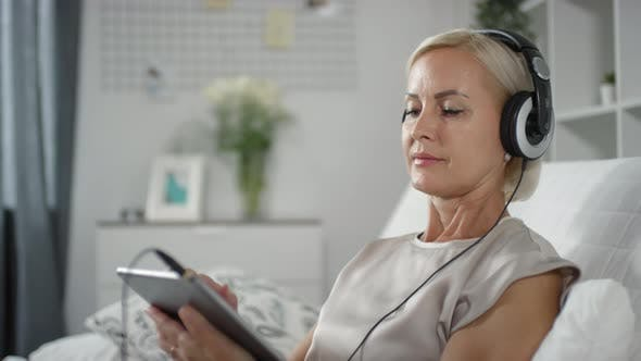 Cheerful Mature Woman Using Tablet and Listening to Music with Headphones