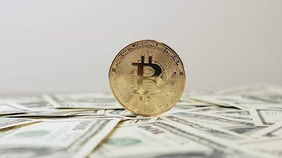 Gold bitcoin rotating on dollar background