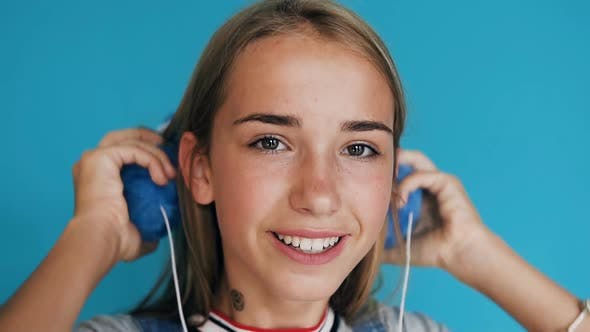 Thumbnail for Teenage Girl Putting on the Headphones Listening to Music and Dancing