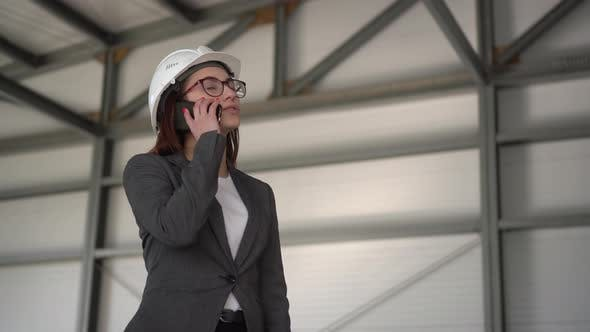 Thumbnail for A Young Woman in a Helmet Speaks on the Phone at a Construction Site. The Boss in a Suit Is Talking