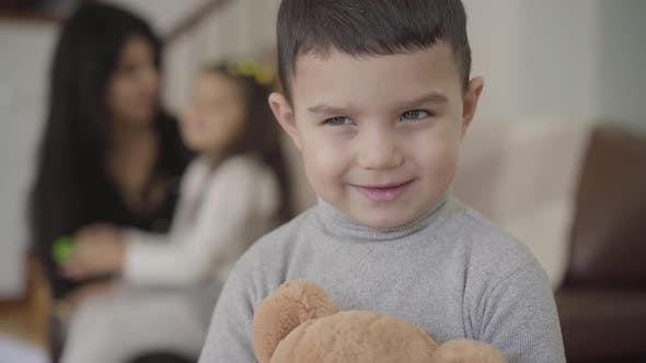 Thumbnail for Close-up Face of a Charming Middle Eastern Grey-eyed Boy with Dark Hair Holding the Teddy Bear