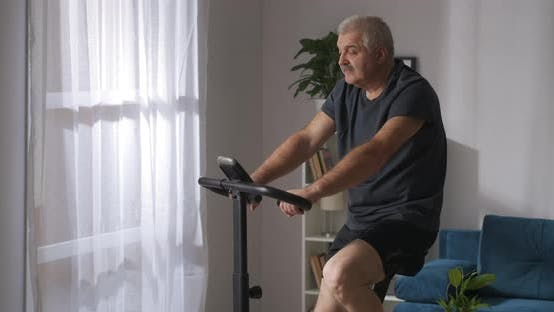 Adult Man Is Losing Weight Training on Exercycle in Home Sport Activity at Selfisolation