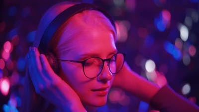 Young Female Dj in Headphones and Glasses Dances to Energetic Music in the Club