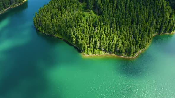 Thumbnail for Mountain lake island with turquoise water and green trees. Reflection in the water.