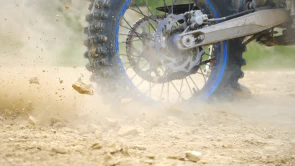 Thumbnail for Close Up Wheel of Powerful Off-road Motorcycle Spinning and Kicking Up Dry Ground or Dust