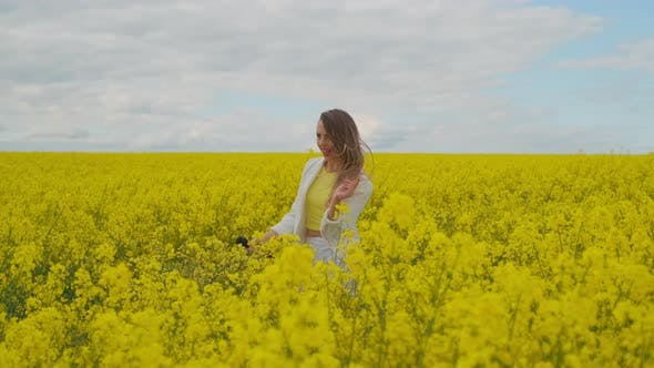 Thumbnail for An Energetic Female Singer with a Microphone in a Field of Rapeseed with Yellow Flowers Jumps Shakes