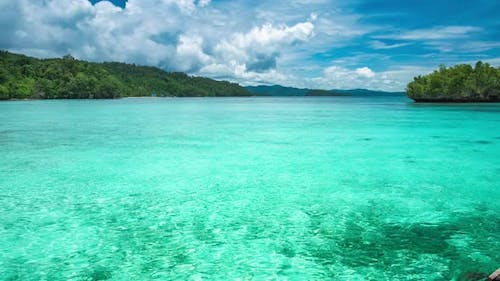 Beautiful Blue Lagoon with Pure Clear Water and Rainy Clouds in Background, Gam Island, West Papua