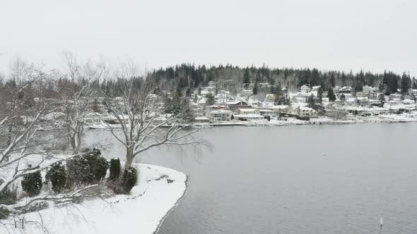 Thumbnail for Snowy Lake Drone Aerial Flying By Tree Waterfront Houses Background