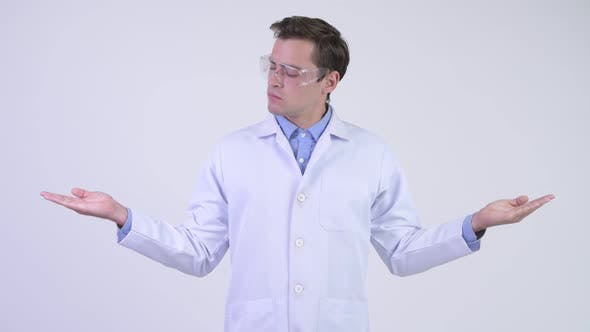 Cover Image for Young Handsome Man Doctor Wearing Protective Glasses and Comparing Something