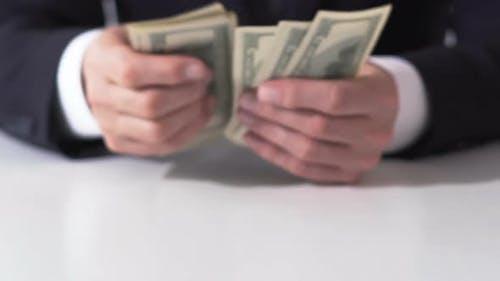 Reicher Mann zählt Dollar-Banknoten, Hände des Geschäftsmannes, der Einkommen schätzt