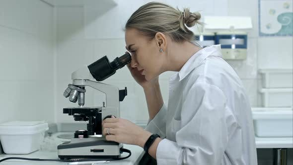 Thumbnail for Surprised Woman Working with a Microscope in Laboratory