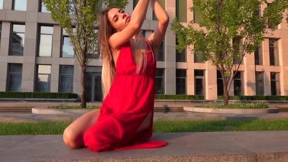 Красивая молодая девушка танцует на улице современного здания бизнес-центра в закате