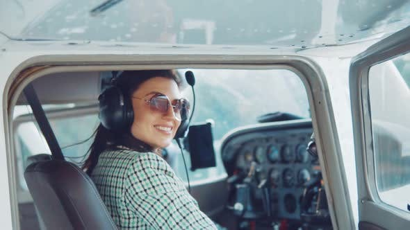 Thumbnail for Portrait of a Young Attractive Girl in an Airplane at the Helm.