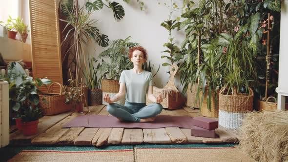 Thumbnail for Young Woman Meditating in Lotus Pose at Home