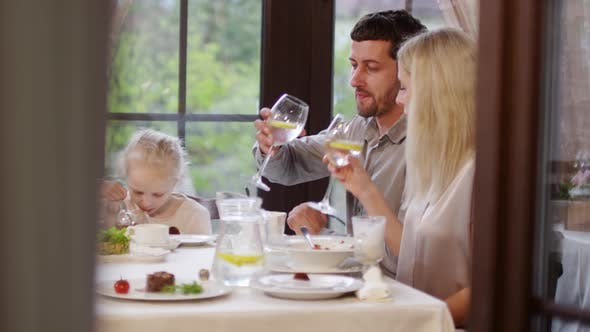 Thumbnail for Married Couple and Child Eating in Restaurant