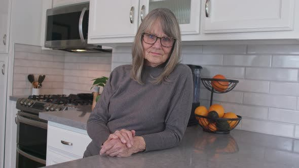 Thumbnail for Grey haired senior woman with glasses looking at camera in her kitchen