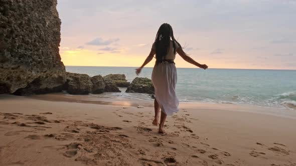 Thumbnail for Brunette Woman in a Dress Running Along Water at Sunset or Sunrise. Happy Carefree Woman Dancing at