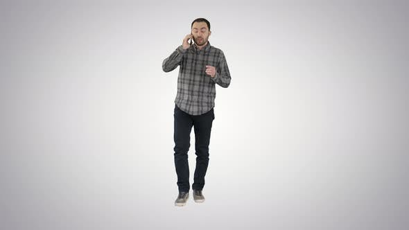 Thumbnail for Serious Man Walking and Talking on His Cellphone on Gradient Background.