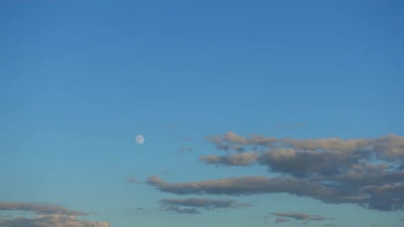 Thumbnail for Time-lapse 4k, the full Moon rise up in the blue sky above the beautiful clouds