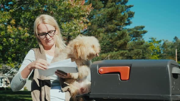 Thumbnail for A Young Woman with a Small Dog in Her Arms Picks Up Letters From a Mailbox