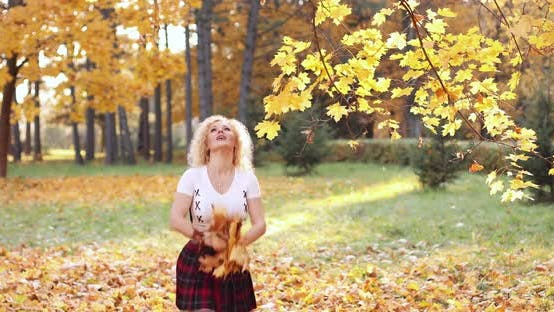 Thumbnail for Happy Blonde Woman in Sexy Crop Top and Skirt Playing with Foliage in Park