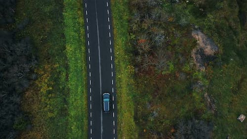Aerial Top View, Drone Zooming in on Black Car Moving Along Highway Road Along Autumn Forest on a