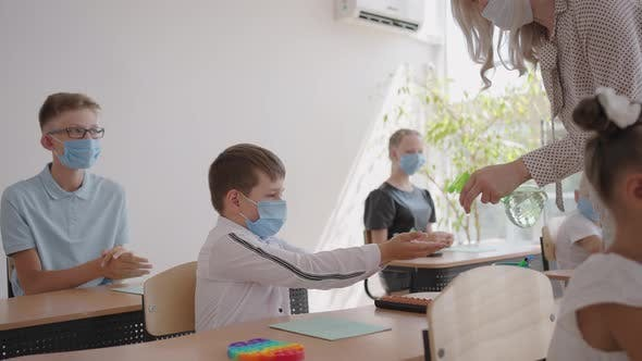 Teacher Children with Face Mask at School After Lockdown Disinfecting Hands