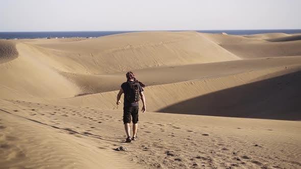Thumbnail for Man Walking In Sand Dunes