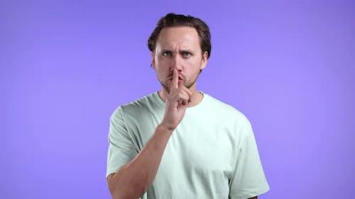 Serious Man Holding Finger on Lips Over Violet Background