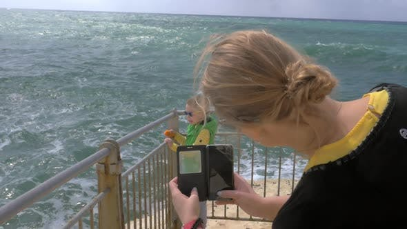 Mom taking cell photo of child looking at sea Rosh Hanikra