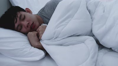 Asian man feeling cold while sleeping at home.