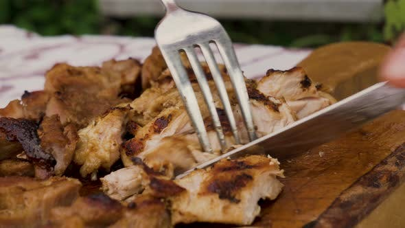 Thumbnail for Hand Holding Knife Cutting Grilled Meat Steak on A Wooden Board
