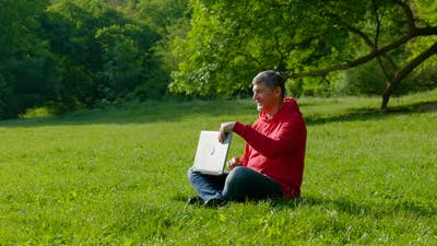 Man Working on Laptop in Summer Forest
