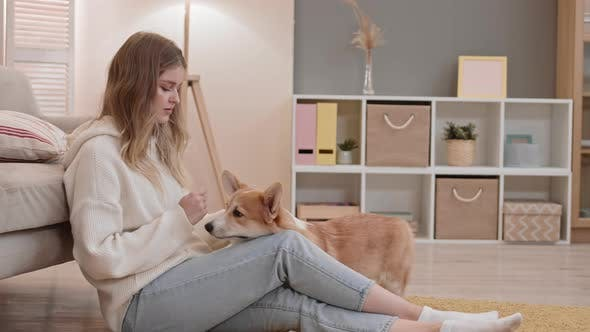 Blond Woman with Corgi at Home