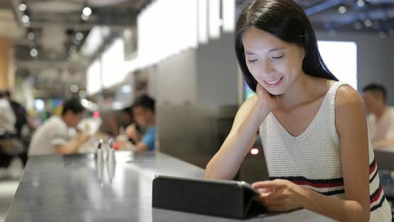 Thumbnail for Woman Using Digital Tablet Computer in Restaurant
