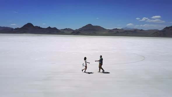 Thumbnail for Cinematic Aerial Shot of Excited Happy Romantic Couple Walking Together, Hugging in Epic Salt Lake