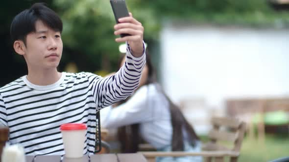 Thumbnail for Asian Teen Boy Taking Selfie in Outdoor Cafe