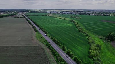Cars Driving Along the Rustic Asphalt Road Between Fields