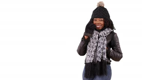 Thumbnail for Attractive black female in cozy hat and scarf waving at camera in studio