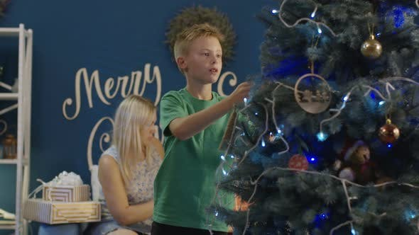 Cover Image for Boy Decorating Christmas Tree at Home