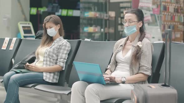 Thumbnail for Young and Mid-adult Caucasian Women in Face Masks Waiting for Departure in Airport, Bus or Railway