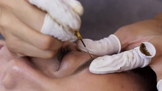 Thumbnail for Beautician hands doing eyebrow microblading with ink needle